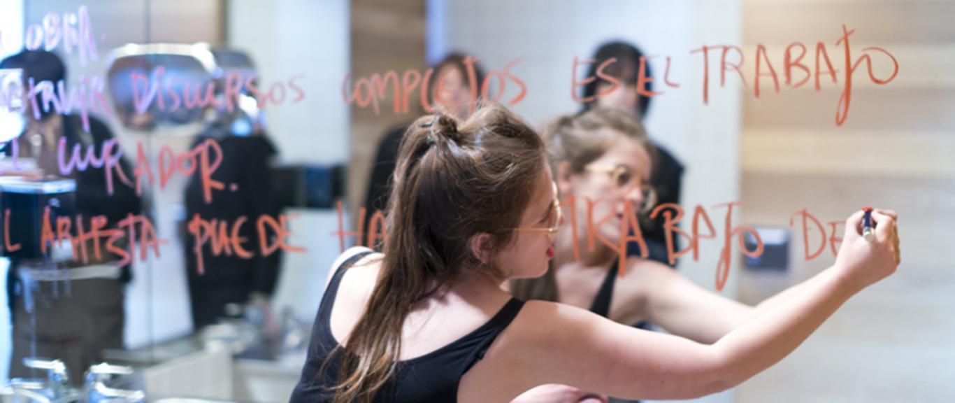 Participante en un taller artístico escribiendo en un espejo