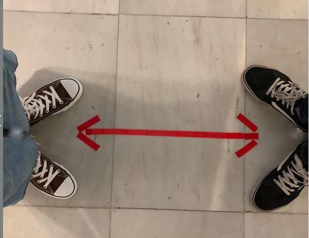 Vista de los pies de dos personas y una flecha entre ellos que parece separarlos
