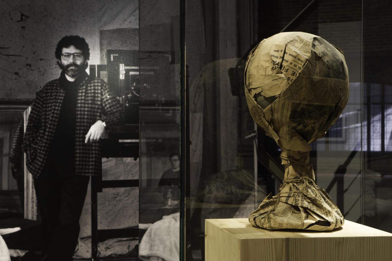 Bola del mundo envuelta en papel de periódico sobre una vitrina. Al fondo, imagen del fotógrafo Toni Catany en su estudio con su cámara de fotos