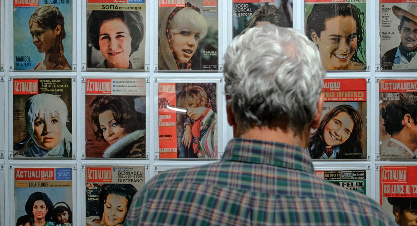 Hombre mirando portada de revistas expuestas en una pared