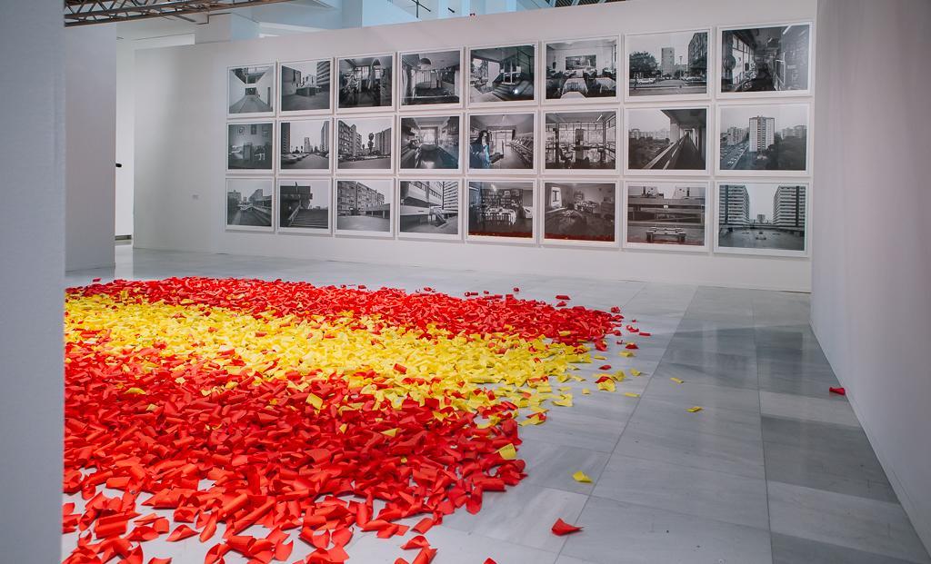 Instalación artística con papeles de colores tirando en el suelo que conforman, por agrupación, la bandera de España. En el fondo una composición fotográfica