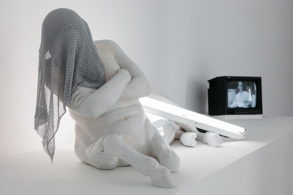 Escultura de un fauno cubierto con una malla metálica. De fondo varios fluorescentes encendidos y amontonados y una televisión que emite un audiovisual