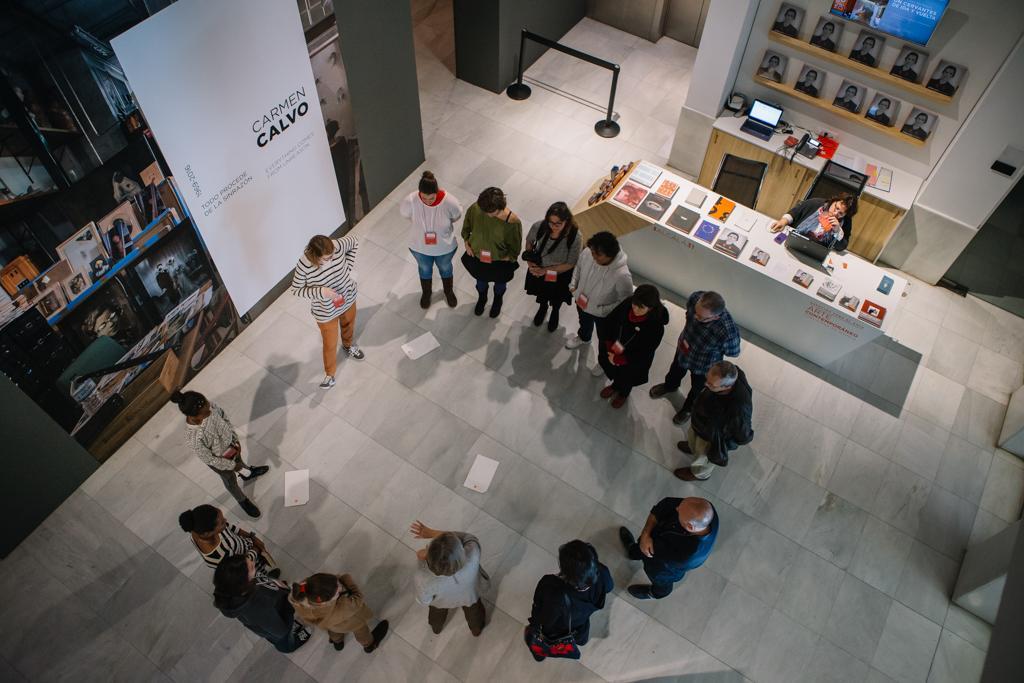 Grupo de personas adultas en círculo haciendo una visita a la expo de Carmen Calvo
