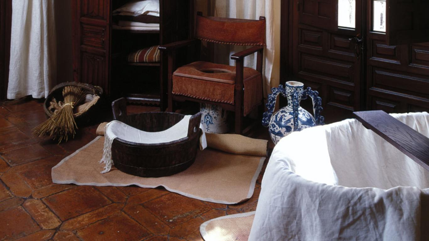 Barreño, silla para wc y toallas en una zona de higiene antigua