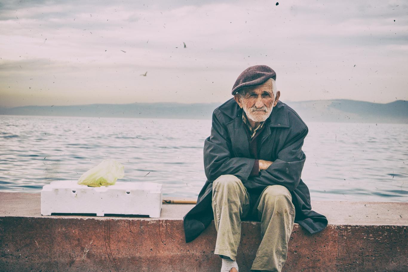Anciano sentado de espaldas al mar