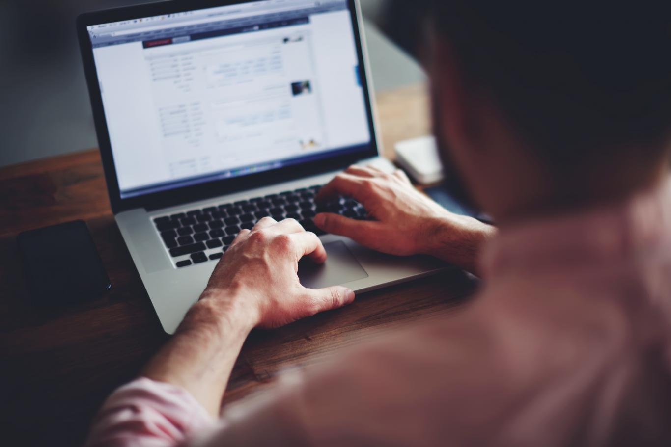 Hombre de espaldas, tecleando en un ordenador portátil