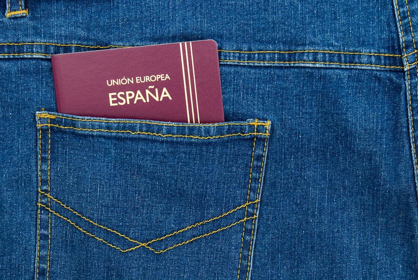 Un pasaporte de España sobresale del bolsillo de un pantalón vaquero