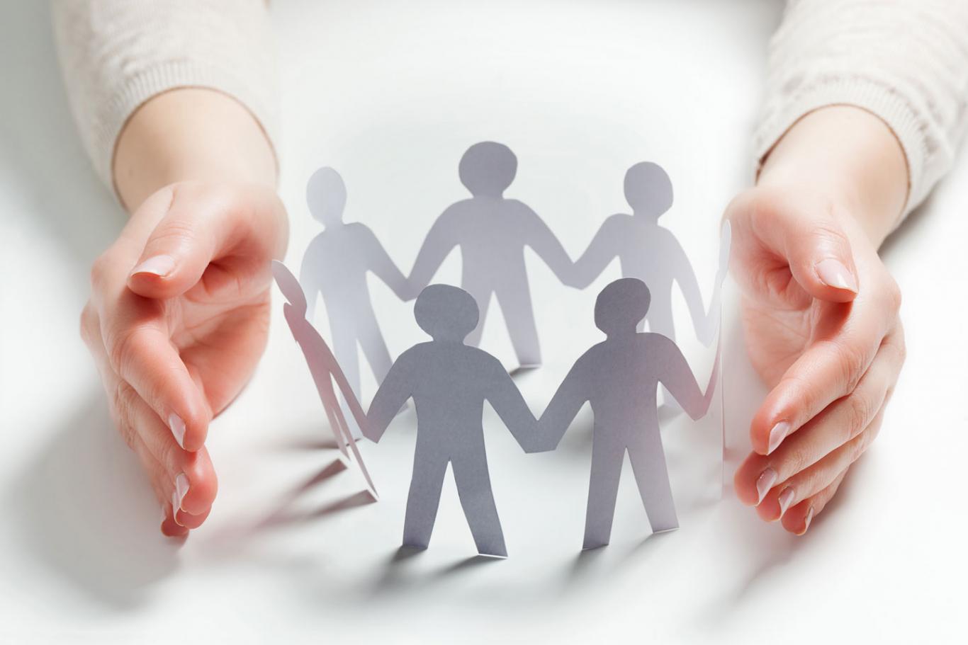 Unas manos enmarcan, protectoras, unas figuras humanas hechas de papel