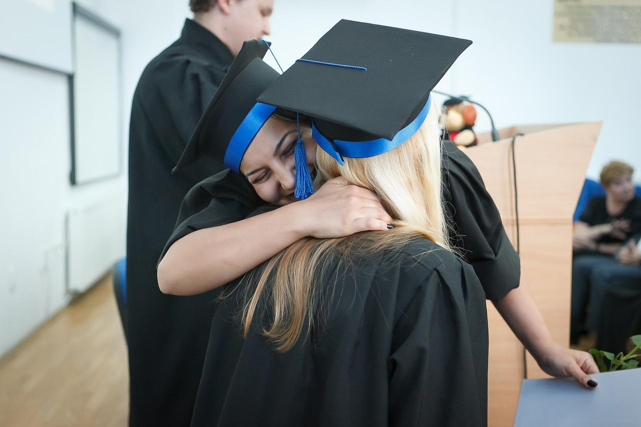 Dos graduadas universitarias abrazándose