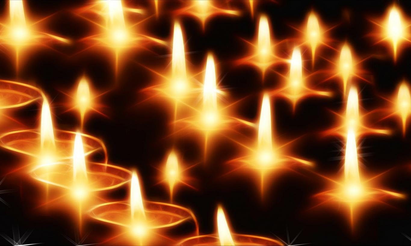 Muchas velas encendidas en un sitio oscuro