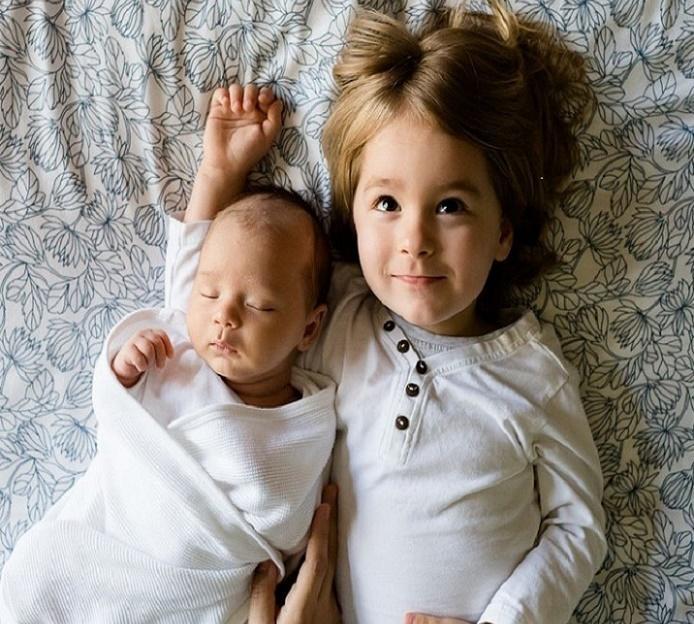 Foto de dos hermanos. El bebé esta a la izquierda y el mayor mira con esperanza