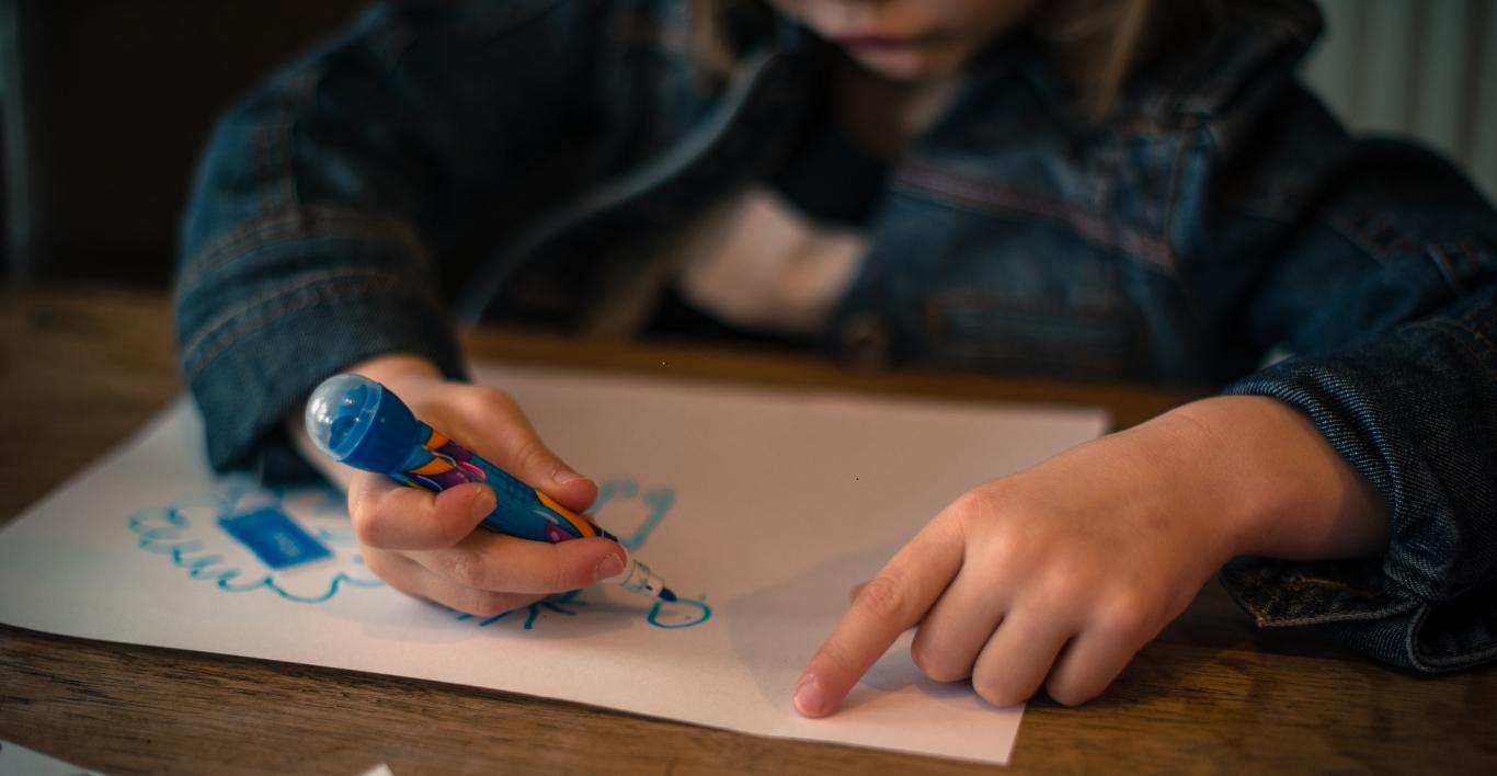 Plano de las manos de un niña dibujando sobre un papel