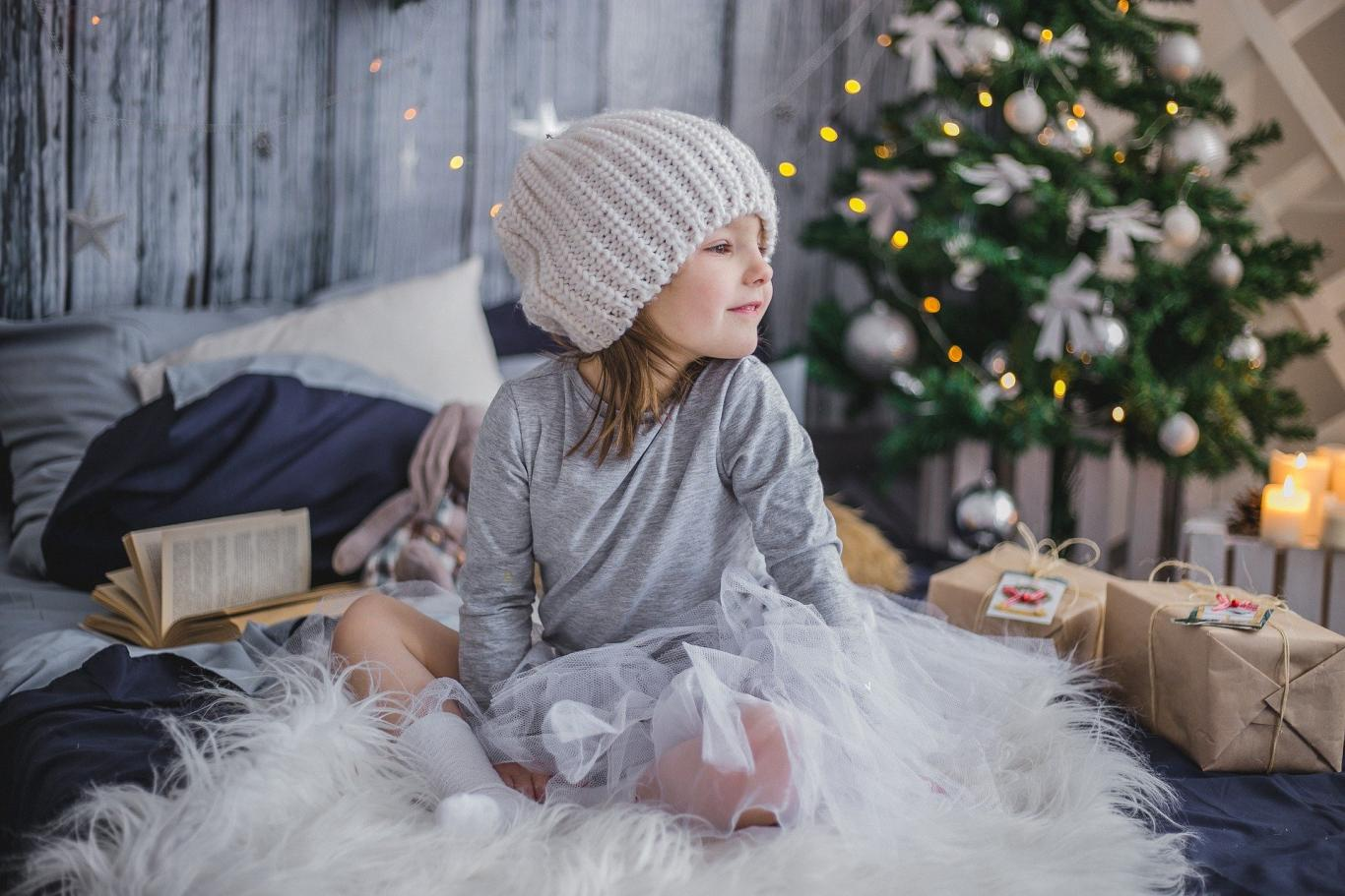 niña pequeña con árbol de Navidad y regalos