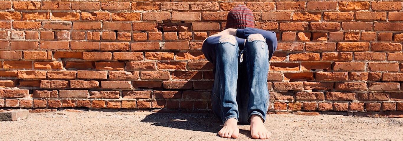 Chico sentado en el suelo apoyado en la pared y tapándose la cara