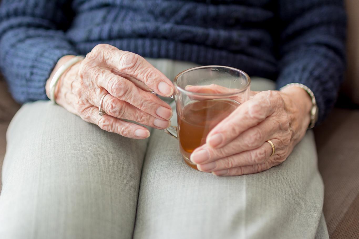 Señora mayor sentada tomando infusión