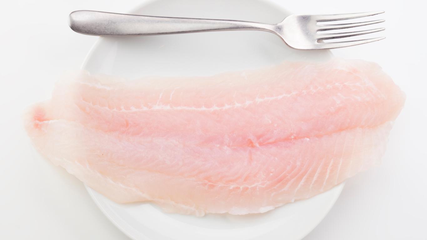 Filete de panga crudo en un plato con un tenedor