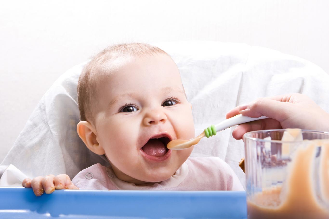 Madre dando de comer a bebé