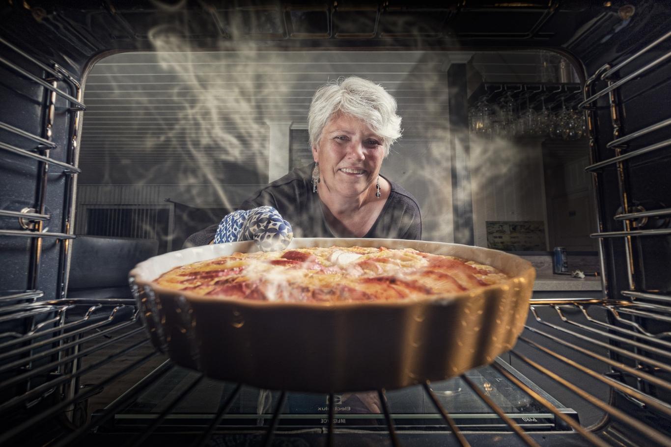 señora sacando del horno una tarta de manzana