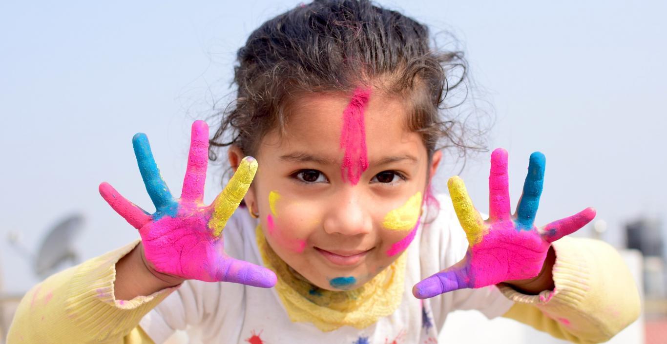 Niña enseñando sus manos pintadas