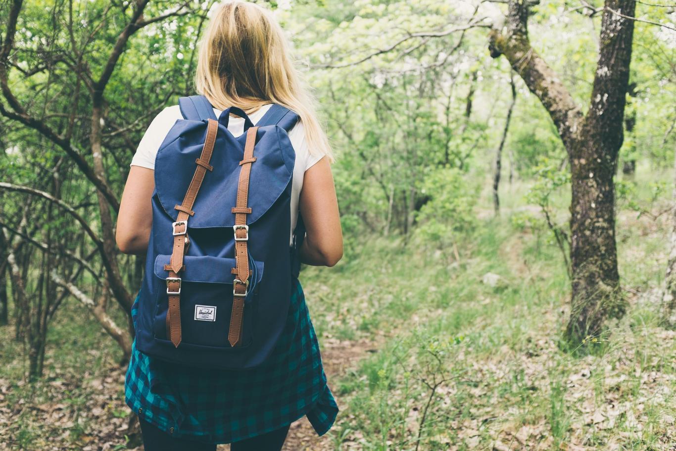 Joven con mochila en el campo