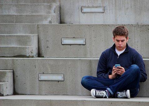 Chico sentado en escolares con móvil