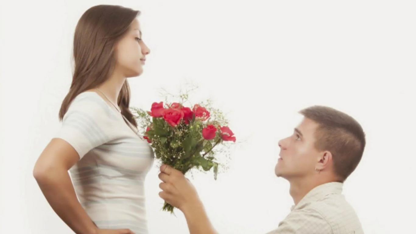 Hombre de rodillas entregando ramo de flores a mujer