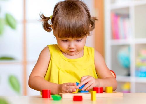 Niña jugando con construcciones de madera