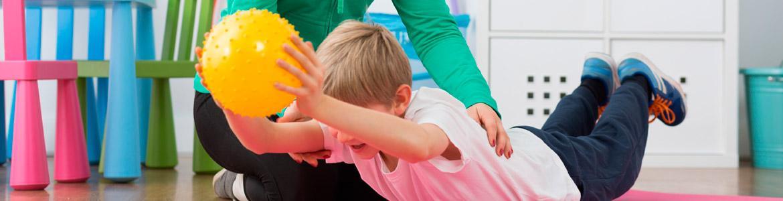 Niño realizando un ejercicio con una pelota