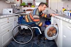 Persona con discapacidad física poniendo la lavadora