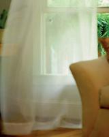 Ventana con cortina y sillón