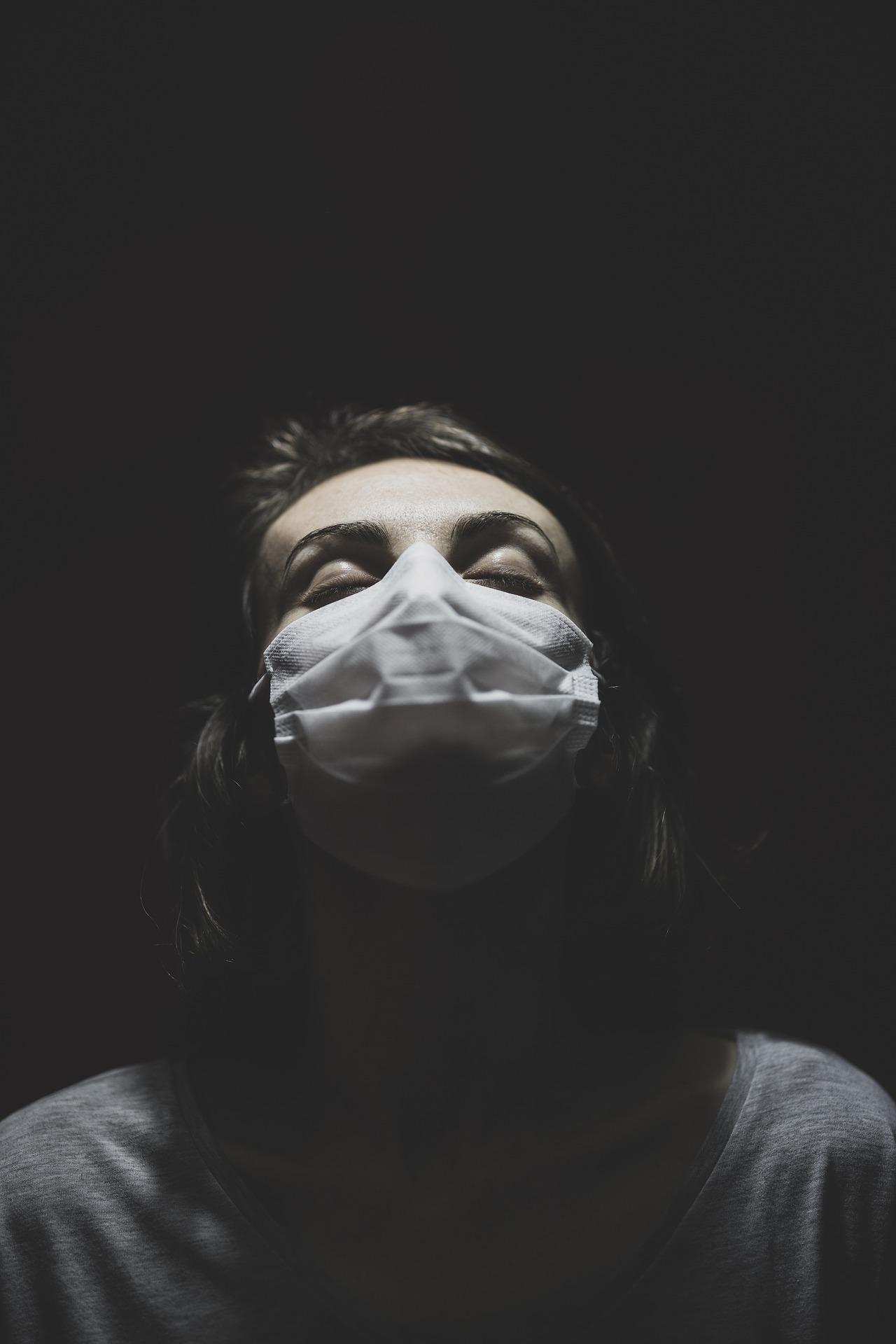 mujer con mascarilla y los ojos cerrados