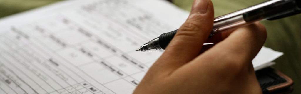 Mano rellenando un formulario con un portaminas negro