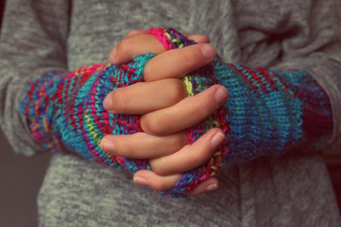 Manos entrelazadas con guantes de colores