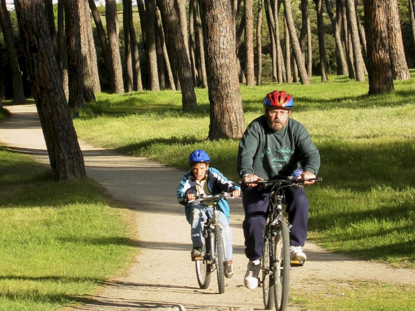Imagen de un hombre y un niño en bicicleta pedaleando en un camino entre árboles