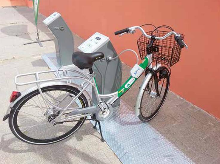 Bicicleta eléctrica pública recargándose en un aparcabicis