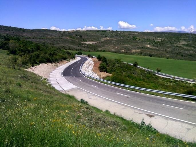 Carretera en el Vellón en obras, con campo verde a ambos lados