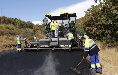 obreros trabajando con maquinaria asfaltando en la M-601