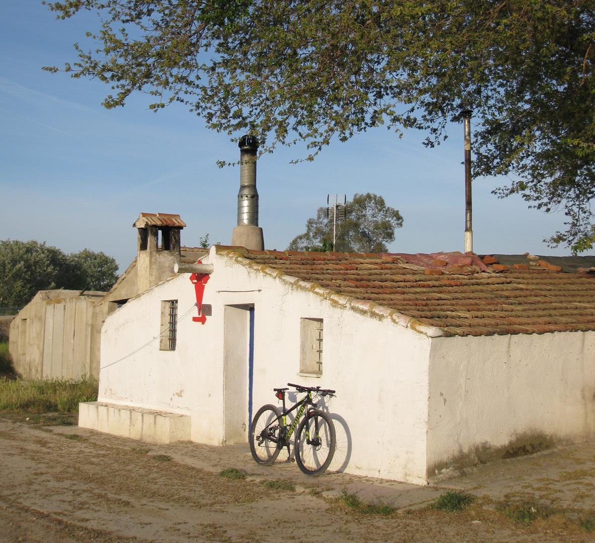 Casita encalada en el camino a Uclés con bicicleta apoyada en su fachada