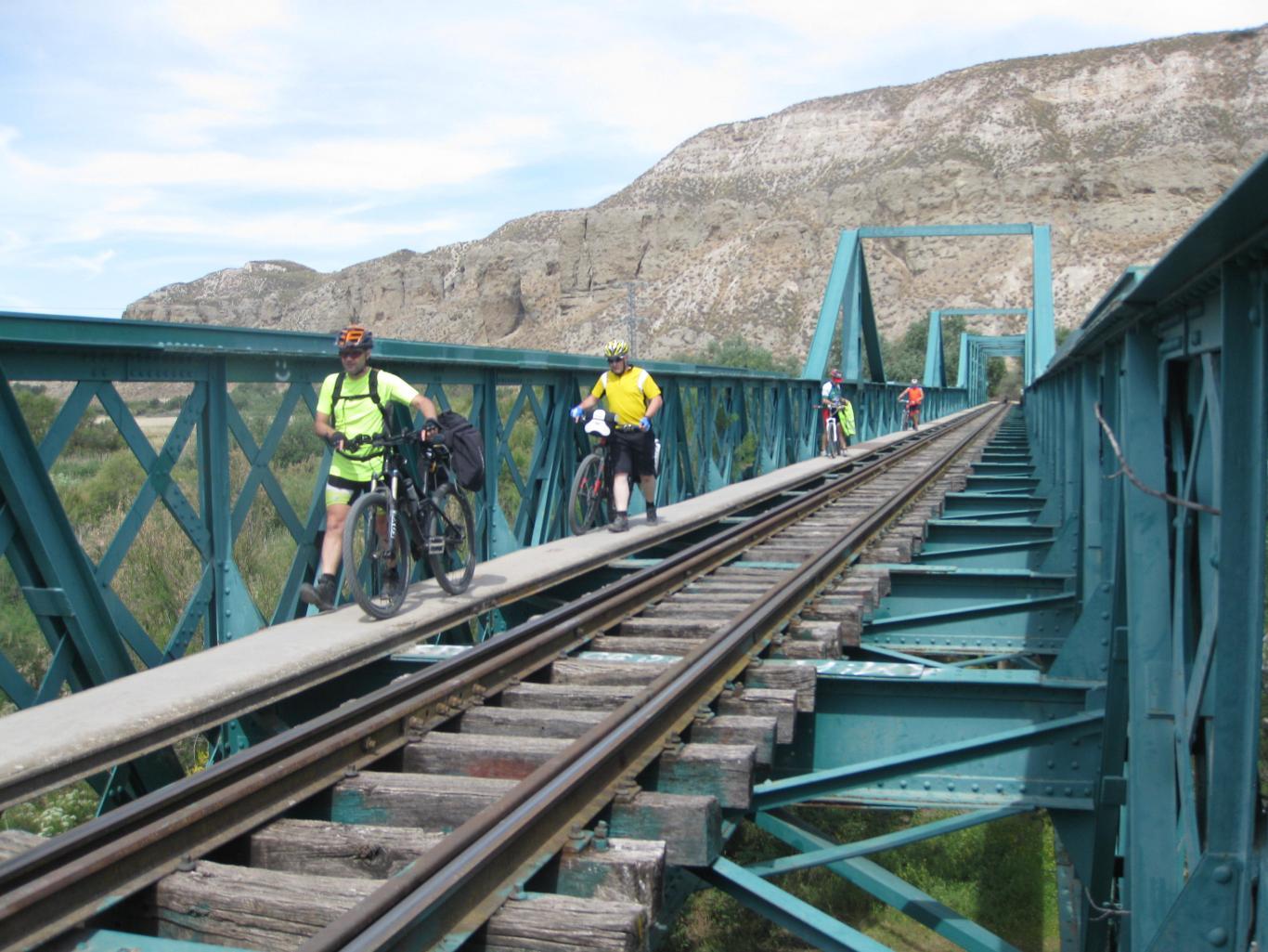 Ciclistas cruzando a pie el puente de hierro del antiguo tren de Arganda, sobre el río Jarama