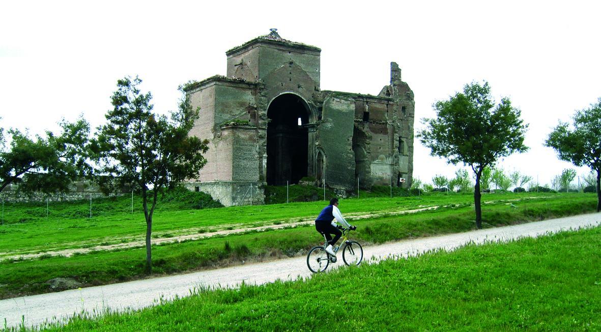 Ciclista pasando por delante de la iglesia de San Pedro, en el Parque Polvoranca