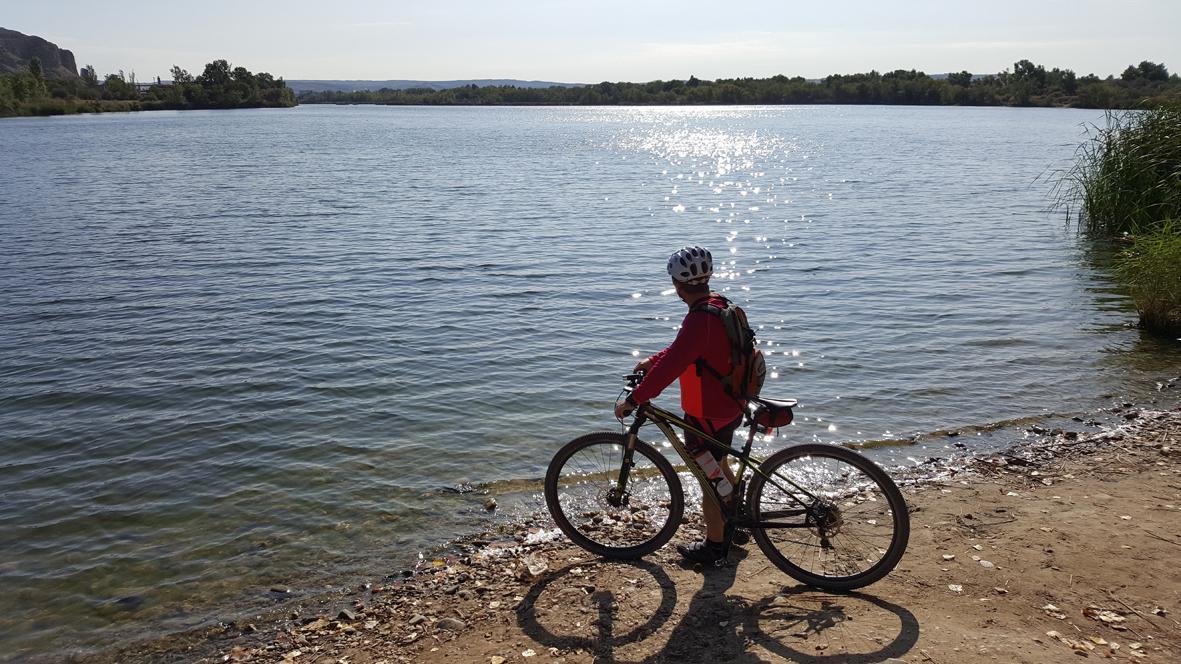 Ciclista parado delante de la laguna del Campillo
