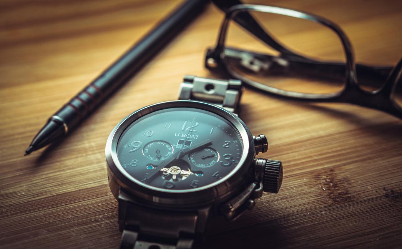 reloj negro de pulsera y gafas sobre fondo de madera con veta paralela madera