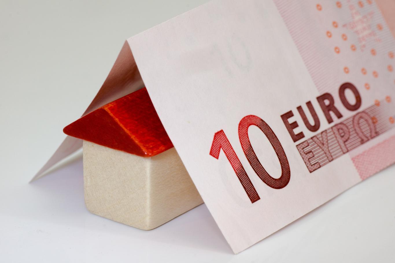 Imagen de casa de madera con billete