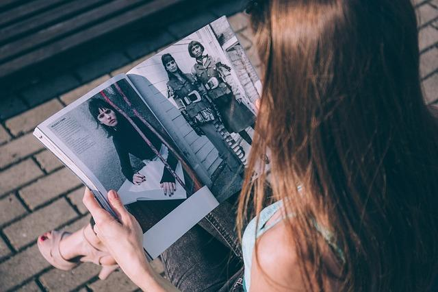 Imagen de una mujer de espaldas leyendo una revista