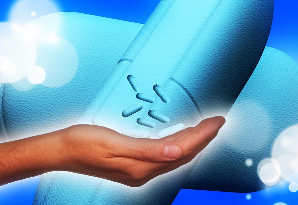 mano sosteniendo unas píldoras de medicamentos