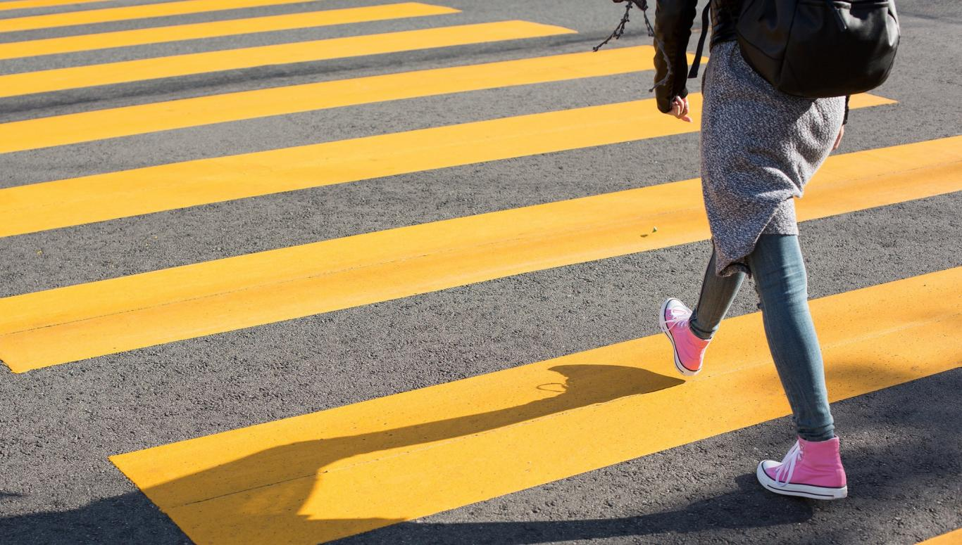 Joven cruzando un paso de cebra amarillo