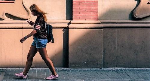 Chica andando por una acera con un móvil
