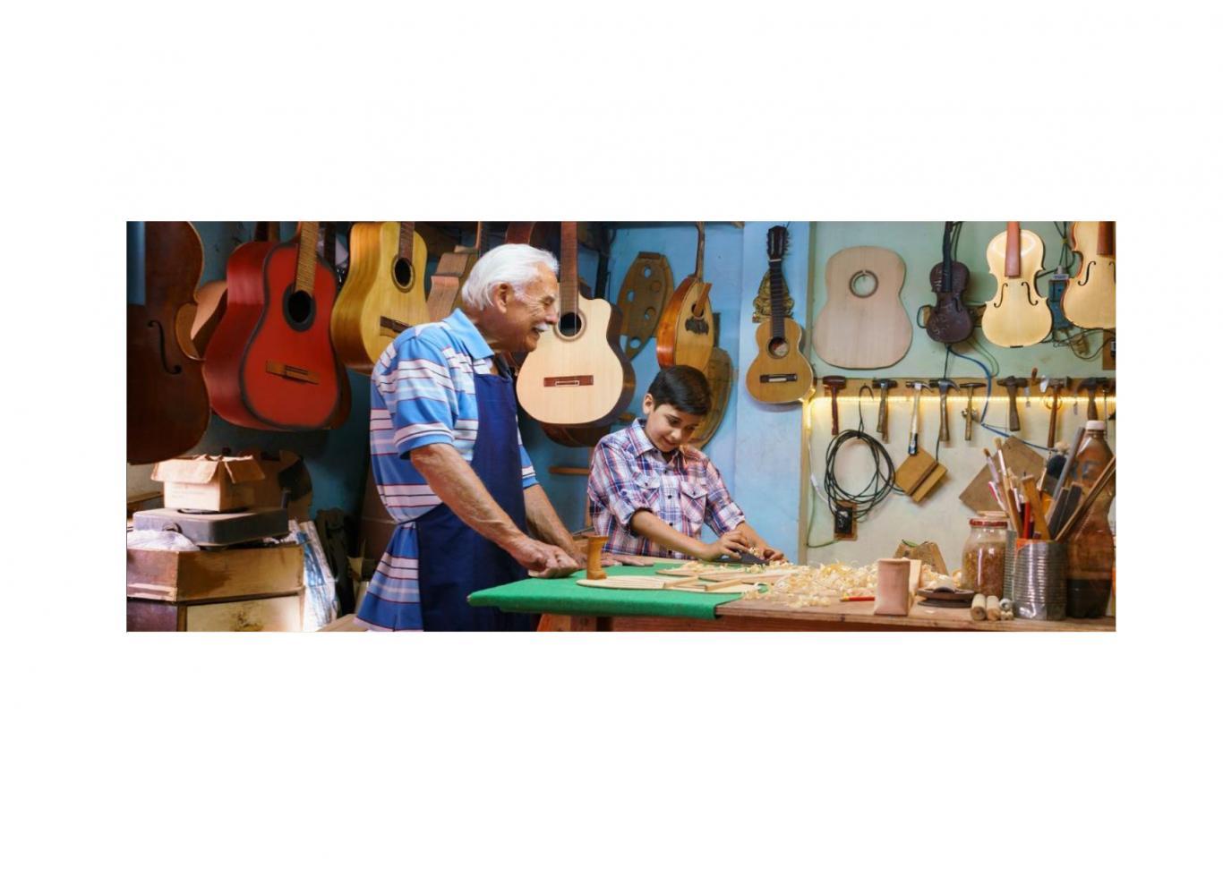 Imagen de una persona mayor y un niño trabajando en un taller artesano de guitarras