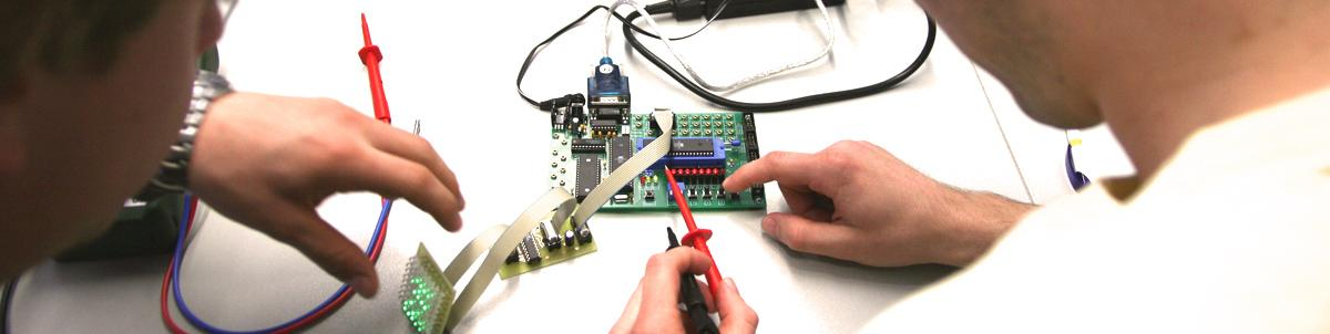 Dos personas trabajan sobre una placa electrónica