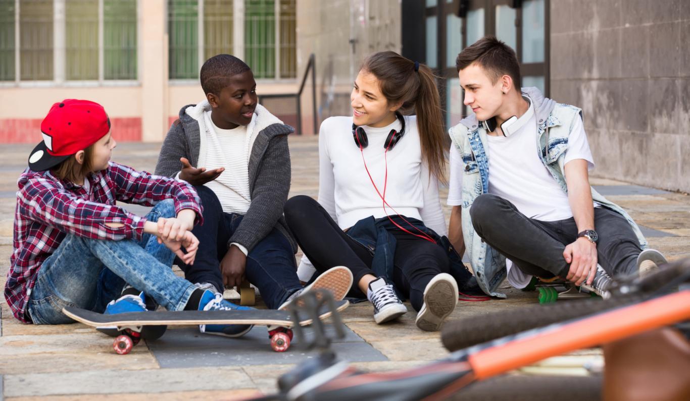 Joven con un grupo de adolescentes sentados en la calle